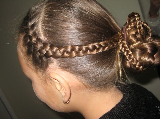 A braided headband tied back into a multi-plaited bun.
