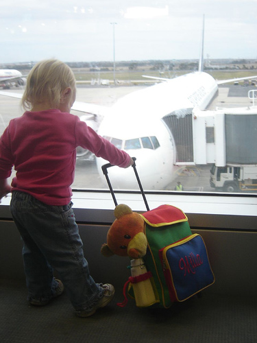 Girl-child and skanky bear waiting to board